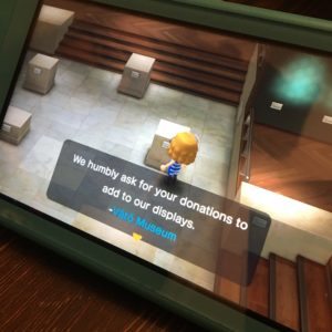 Screenshot of ACNH player's avatar looking at an empty pedestal in a museum gallery. A message appears encouraging the player to donate artifacts to the museum.